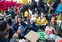 © Licensed to London News Pictures. 09/10/2019. London, UK. Campaigners from the Extinction Rebellion movement are seen breastfeeding as they take part in a mass nurse-in protest in Westminster on day three of the two weeks protest. The activists are calling for the government to act on climate change. Photo credit: Dinendra Haria/LNP