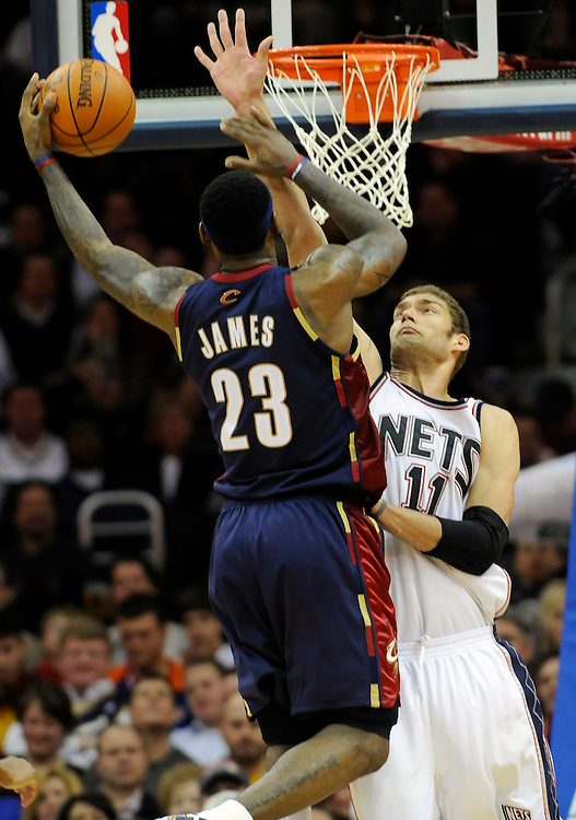 Dec 15, 2009; Cleveland, OH, USA; Cleveland Cavaliers forward LeBron James (23) shoots over New Jersey Nets center Brook Lopez (11) during the third quarter at Quicken Loans Arena. The Cavaliers beat the Nets 99-89. Mandatory Credit: Jason Miller-US PRESSWIRE