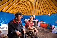 Mongolian farmers in thier yurt used for processing mares milk and temporary sleeping.