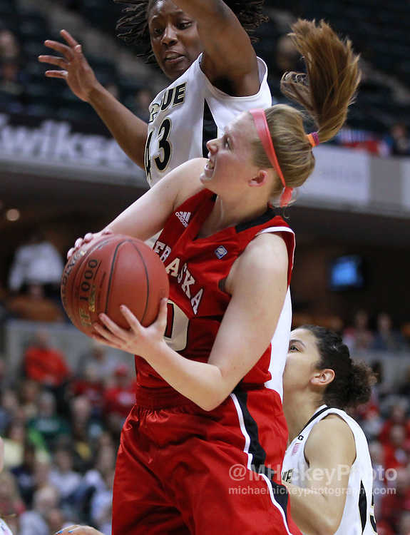 March 04, 2012; Indianapolis, IN, USA; Purdue Boilermakers guard Chantel Poston (43) defends as Nebraska Cornhuskers guard Lindsey Moore (00) shoots the ball during the finals of the 2012 Big Ten Tournament at Bankers Life Fieldhouse.  Mandatory credit: Michael Hickey-US PRESSWIRE