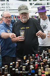 Olympia, London, August 9th 2015. Hundreds of real ale lovers attend the Campaign for Real Ale  Great British Beer Festival at London's Olympia Exhibition Centre, where dozens of independent breweries demonstrate the diversity of British brewed beers. PICTURED: Dozens of different bottled beers are available for sampling.