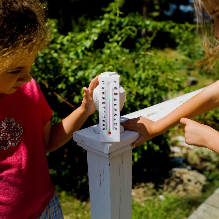 Girls using thermometer to measure outdoor temperature.