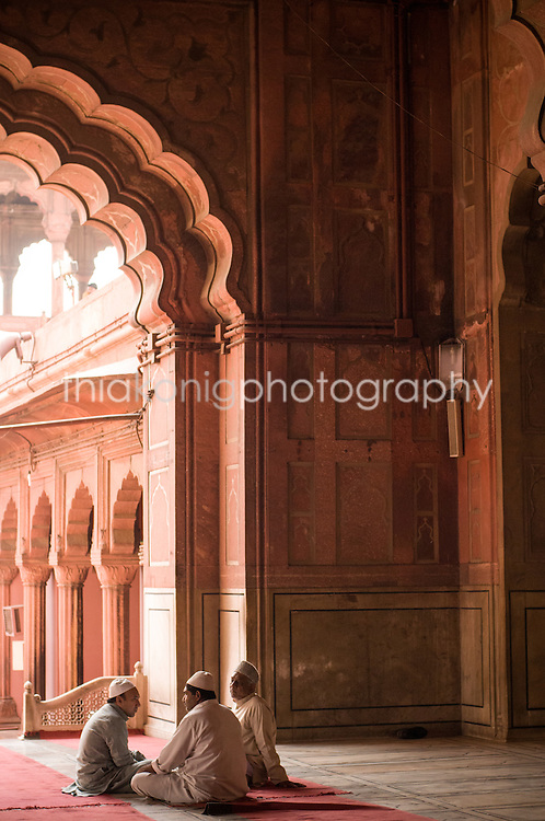 Three men sit in a circle in Jama Masjid, a Muslim mosque near the Red Fort in Delhi, India.