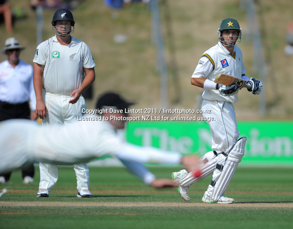 Pakistan captain Misbah ul-Haq (right) and NZ's Jesse Ryder watch as Brendan McCullum dives for the ball.  2nd cricket test match - New Zealand Black Caps v Pakistan, day three at the Basin Reserve, Wellington, New Zealand on Monday, 17 January 2011. Photo: Dave Lintott / photosport.co.nz