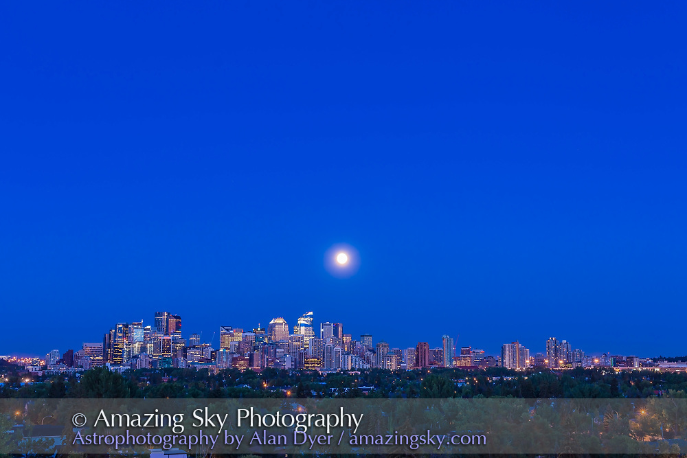 "The Full Moon of July 31 2015, an infamous ""Blue Moon,"" rising over the skyline of Calgary, in a wide view taken with the 50mm lens and Canon 6D, as one frame of a 480-frame time-lapse. The location was Toronto Crescent."