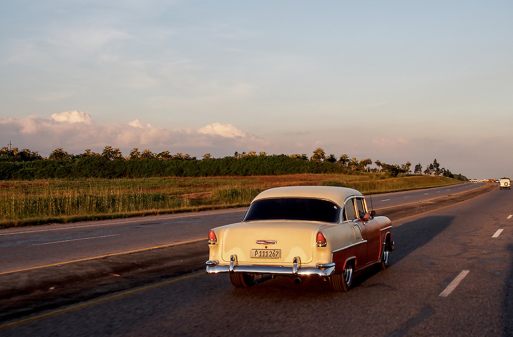 A 1950's, perhaps, Chevy drives up the very empty freeway between Vinales and Havana. Most people are too poor to own their own car so most of the cars in Cuba are used for driving tourists around. Travel images from Havana Cuba. Pictures by Chris Pavlich Photography.