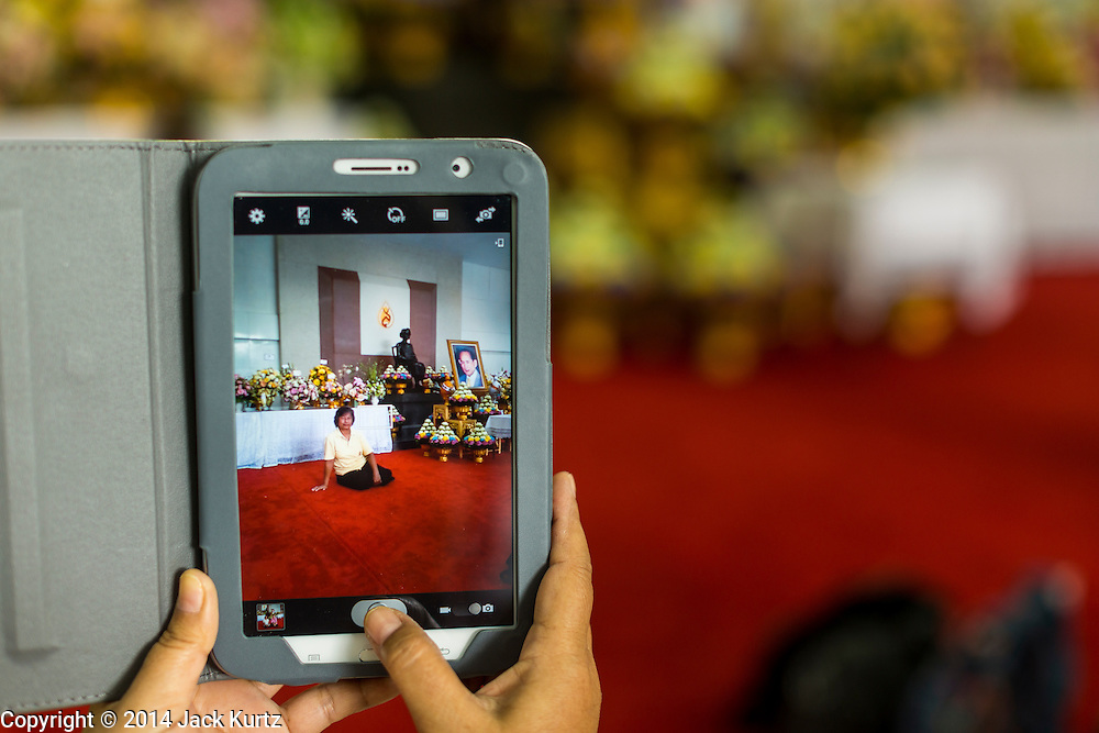 09 OCTOBER 2014 - BANGKOK, THAILAND: People use smart phones to photograph themselves in front of a portrait of Bhumibol Adulyadej, the King of Thailand in the lobby of SIriraj Hospital. The King has been hospitalized at Siriraj Hospital since Oct. 4 and underwent emergency gall bladder removal surgery Oct. 5. The King is also known as Rama IX, because he is the ninth monarch of the Chakri Dynasty. He has reigned since June 9, 1946 and is the world's longest-serving current head of state and the longest-reigning monarch in Thai history, serving for more than 68 years. He is revered by the Thai people and anytime he goes into the hospital thousands of people come to the hospital to sign get well cards.   PHOTO BY JACK KURTZ