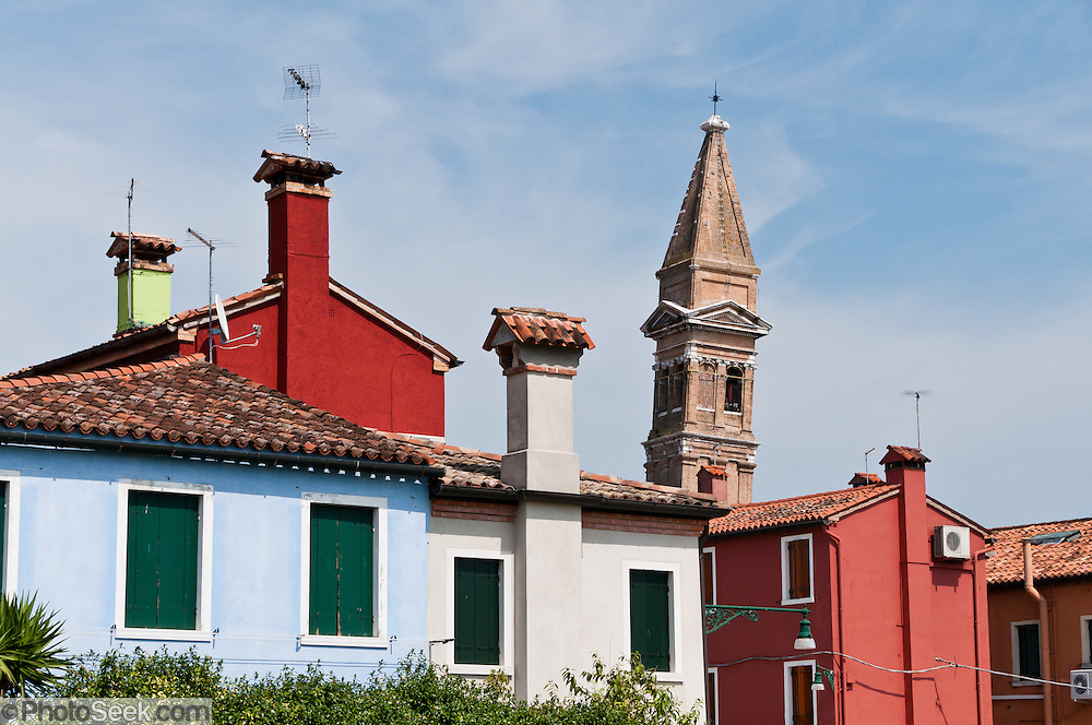 "The tilting campanile of the Church of San Martino contrasts with upright houses in Burano, Italy. Burano, known for knitted lacework, fishing, and colorfully painted houses, is a small archipelago of four islands linked by bridges in the Venetian Lagoon, northern Italy, Europe. Burano's traditional house colors are strictly regulated by government. The Romans may have been first to settle Burano. Romantic Venice (Venezia), ""City of Canals,"" stretches across 100+ small islands in the marshy Venetian Lagoon along the Adriatic Sea in northeast Italy, between the mouths of the Po and Piave Rivers. Venice and the Venetian Lagoons are on the prestigious UNESCO World Heritage List."