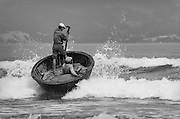 Vietnam, China Beach. Two men are in a round fishing boat made out of bamboo and tar. One of them is standing up and rowing the boat against breaking ocean waves with a single oar.