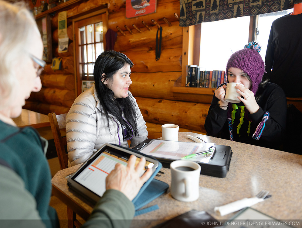 Students Heidi Kattenhorn (center) and Allison Stuart (right) warm up during a hot chocolate break at the 33 Mile Roadhouse after completing the weekly bald eagle count. While Kattenhorn and Stuart warm up, Pam Randles, Takshanuk Watershed Council Education Director, enters the bald eagle count totals into her tablet computer. Since 2009, students have been conducting a weekly count of bald eagles during the fall semester for the citizen science class at the Haines School. The project is part of a field-based for-credit class, sponsored by the Takshanuk Watershed Council, in which students participate in research studies and learn about field data collection. Under the guidance of Pam Randles, Takshanuk Watershed Council Education Director, students count bald eagles in the Chilkat River Valley using spotting scopes at 10 locations and present their data at the Bald Eagle Festival held in November in Haines. During late fall, bald eagles congregate along the Chilkat River to feed on salmon. This gathering of bald eagles in the Alaska Chilkat Bald Eagle Preserve is believed to be one of the largest gatherings of bald eagles in the world.