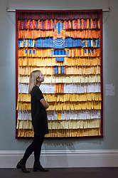 "© Licensed to London News Pictures. 23/03/2018. LONDON, UK. A staff member views ""Femme Du Sahel"" by Abdoulaye Konate (Est. GBP25,000-30,000).  Preview of Modern and Contemporary African Art sale at Sotheby's, New Bond Street.  The auction will take place on 28 March 2018.   Photo credit: Stephen Chung/LNP"