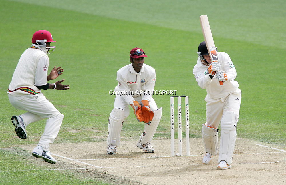 West Indies fielder Dwayne Bravo leaps in the air as wicketkeeper Denesh Ramdin lools on as New Zealand batsman Brendon McCullum hits out on day 3 of the first cricket test between New Zealand and the West Indies at Eden Park, Auckland, Saturday 11 March, 2006. Photo: Andrew Cornaga/PHOTOSPORT<br />