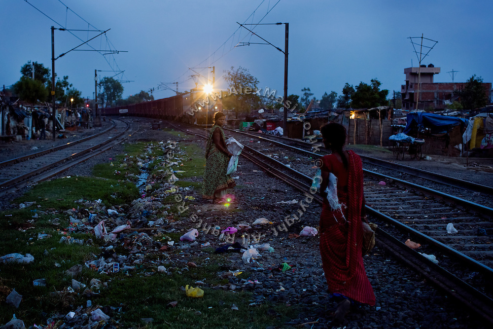 In the early morning, while a train is approaching, two women are collecting pieces of coal fallen on the railway tracks in New Arif Nagar, one of the water-affected colonies standing next to the abandoned Union Carbide (now DOW Chemical) industrial complex, site of the infamous 1984 gas tragedy in Bhopal, Madhya Pradesh, central India. The poisonous cloud that enveloped Bhopal left everlasting consequences that today continue to consume people's lives.