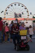Gary and Marilyn Brennfoierder of Edgar, Neb., share a scooter as they cruise the Nebraska State Fair Friday evening in Grand Island. (Independent/Matt Dixon)