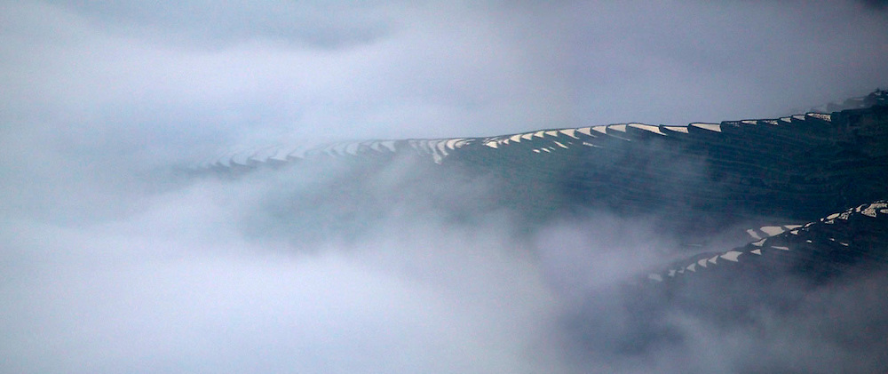 Landscape of water filled rice terraces in mist in the mountain, Yuanyang, Yunnan Province, China