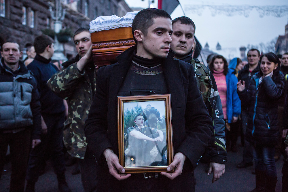 KIEV, UKRAINE - FEBRUARY 21: The body of Ustim Holodnyuk, 19, who was killed in fighting between anti-government protesters and police, is carried from Independence Square on February 21, 2014 in Kiev, Ukraine. After a week that saw new levels of violence, with dozens killed, opposition and government representatives reached an agreement intended to resolve the crisis. (Photo by Brendan Hoffman/Getty Images)