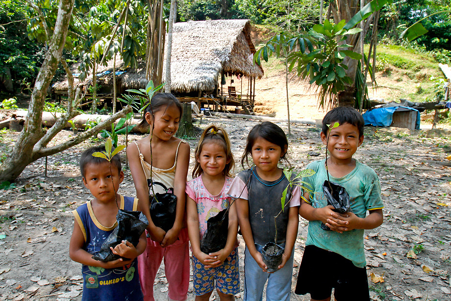 Children with hard wood seedlings in Amazon River village in Peru