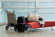 Passenger sleeping on bench in Miami International Airport, Miami, Florida.