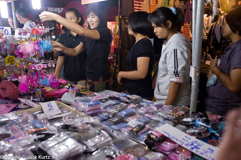 21 FEBRUARY 2008 -- KANCHANABURI, THAILAND: People shop for clothes in the night market in Kanchanaburi, Thailand. Thailand's night markets are popular with Thais and tourists alike because they offer bargains in fake designer clothes and watches and a huge variety of inexpensive foods. Photo by Jack Kurtz/ZUMA Press