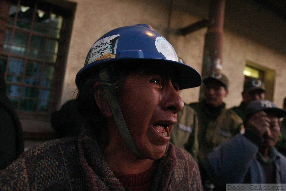 Claudia Ramos shouts as she sees a coffin with a coworker arrive inside Huanuni Mining Enterprise  at the mining city of Huanuni, some 150 kilometers southeast of capital La Paz, Bolivia on Thursday, Oct. 5, 2006. A confrontation between state-employed and independent miners over access to a large tin vain in Bolivia's Oruro region has left at least four dead and more than two dozen injured. Independent cooperative miners on Thursday morning took control of the state owned Huanuni mine to demand more access to its tin deposits, among the largest in the world.(AP Photo/Dado Galdieri)