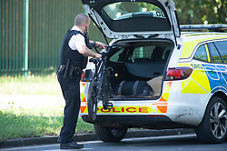 ©Licensed to London News Pictures 26/06/2020<br /> Orpington, UK. A police officer removing a bike from the scene that belongs to one of the attackers. Coronavirus lockdown is over and crime is back on our streets. A gang of six youths on bikes have attacked a man in Orpington,South East London this afternoon. Police, paramedics and the London Air Ambulance attended the scene to find a man with head injuries and covered in blood. Photo credit: Grant Falvey/LNP