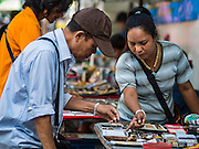 27 NOVEMBER 2015 - BANGKOK, THAILAND: An amulet vendor points out an amulet to a potential customer at her street stall on Maharat Road. Hundreds of vendors sell amulet and Buddhist religious paraphernalia to people in the Amulet Market, a popular tourist attraction along Maharat Road north of the Grand Palace near Wat Maharat in Bangkok. Bangkok municipal officials announced that they are closing the market and forcing vendors to relocate to an area about one hour outside of Bangkok. The closing of the amulet market is the latest in a series of municipal efforts to close and evict street vendors and markets from areas that have potential for redevelopment. The street vendors will be evicted from the area by Sunday, Nov. 29.    PHOTO BY JACK KURTZ