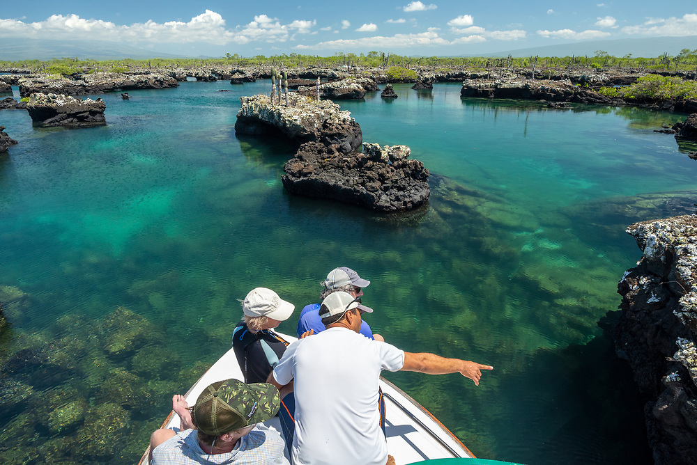Group on the bow of a boat on the coast of Isabela Island, Galapagos Islands, Ecuador.