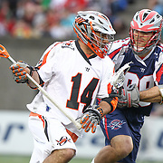Justin Pennington #14 of the Denver Outlaws keeps the ball from Paul Rabil #99 of the Boston Cannons during the game at Harvard Stadium on May 10, 2014 in Boston, Massachusetts. (Photo by Elan Kawesch)