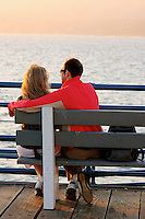 A young couple sits on the bench of the Santa Monica Pier and enjoying each others  and the late afternoon sun .