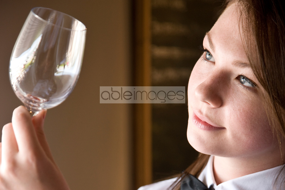 Close up profile of a waitress inspecting a wine glass