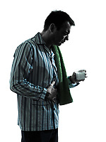 one man man pajamas taking medicine effervescent stomach ache pain in pajamas silhouettes on white background