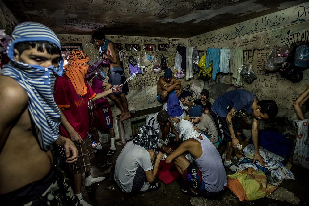 GREATER CARACAS, VENEZUELA – MARCH 6, 2018:  14 prisoners in an overcrowded 3x4 meter cell in a jai located lon the outskirts of Caracas.  One of the prisoners, 22-year old Francisco arrived to the jail healthy, he said – but he has lost over 20 kilos since being locked up. He feels weak all the time and has an incessant cough – coughing up blood and dark phlegm every day. He and the other prisoners believe he has tuberculosis – and fear they will all fall ill by being locked in such a small space together with no air cirulation, and poor sanitary conditions.  Several prisoners have protested by cutting themselves in order to get attention from the prison ministry to get them transferred to a prison – where they will have more space and fresh air. Tuberculosis is on the rise in Venezuela, and especially in jails and prisons.  PHOTO: Meridith Kohut for The New York Times