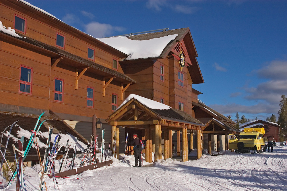 Old Faithful Snow Lodge in winter, with snow coach and skis at entrance; Yellowstone National Park, Wyoming.