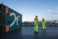 © Licensed to London News Pictures . 05/12/2013 . Manchester , UK . Traffic officers stand on the motorway at the rear of the overturned lorry . An overturned lorry on the Barton Bridge on the M60 orbital road around Manchester as very high winds causes damage across the UK . Photo credit : Joel Goodman/LNP
