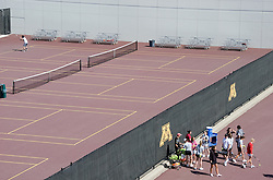 A man practices alone against a wall while a group of tennis Players get ready to practice on the opposite side of the fence at the University of Minnesota