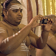 Pujari taking photo in his mobile during South Indian Traditional Tamil Brahmin Wedding