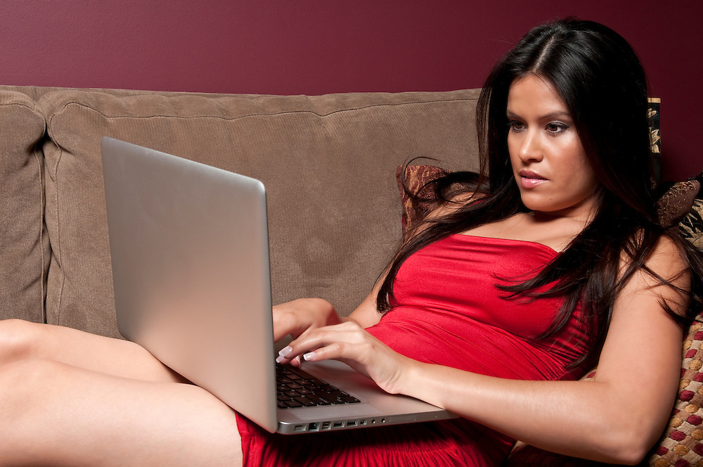 Young hispanic woman looking her computer on a sofa.