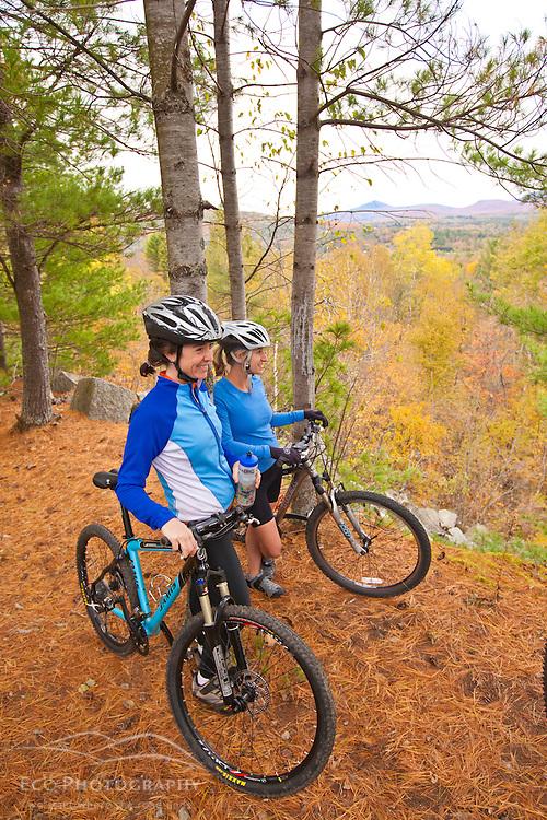 Women mountain biking on a trail on Millstone Hill in Barre, Vermont.  Abandoned granite quarry.  Fall. Millstone Trail Association.