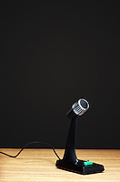 Old fashioned microphone on desk black background