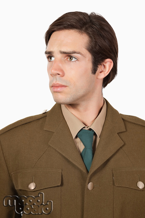 Thoughtful man in military uniform looking away against gray background