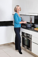 Portrait of happy senior woman preparing food in kitchen