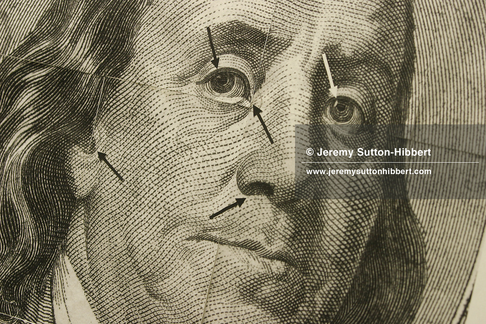 """A copy of a fake American dollar bank note, bearing the face of President Benjamin Franklin, with arrows pointing to mistakes showing this note to be a fake. Matsumura Technology Co. Ltd, a Japanese company specializing in machines to detect counterfeit currencies. The machine can detect fake American dollar bank notes, Euros, and Japanese Yen. The 'Matsumura 4 + 1' counterfeit currency detection machine retails for 4,500 USD, and can detect the best fake notes such as the American dollars """"Super K"""", and """"Super Z"""" fakes."""
