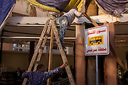 Workmen repair the facade of a restaurant in Luxor, Nile Valley, Egypt.