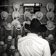 Elderly man standing in front of a huge selection of hats in one of the shops in San luis potosi