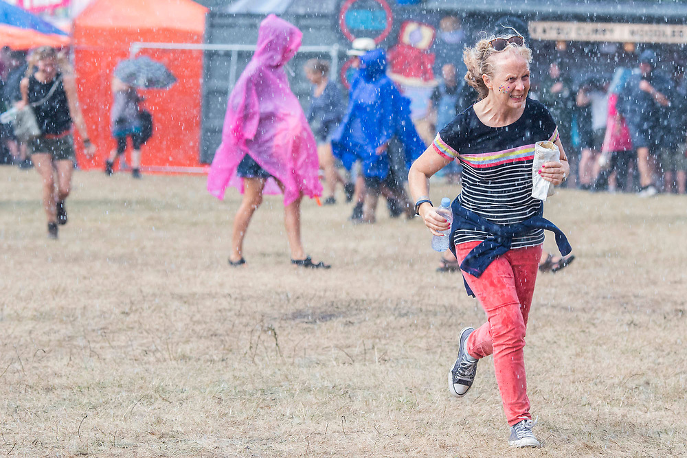 Henham Park, Suffolk, 20 July 2019. The rain falls and people dash for cover - The 2019 Latitude Festival.