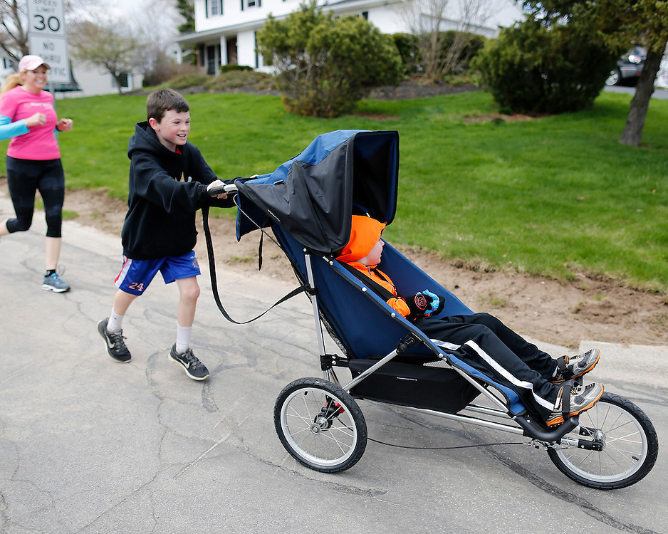 Ryan Mogauro, 12, of Pittsford, pushes Myles Stefl, 13, of Chili, during a group run with Ainsley's Angels on Sunday, April 26, 2015.