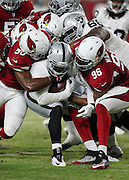 Oakland Raiders running back Jamize Olawale (49) gets gang tackled by Arizona Cardinals linebacker Gabe Martin (50) and Arizona Cardinals linebacker Kareem Martin (96) as he runs the ball in the first quarter during the 2016 NFL preseason football game against the Arizona Cardinals on Friday, Aug. 12, 2016 in Glendale, Ariz. The Raiders won the game 31-10. (©Paul Anthony Spinelli)