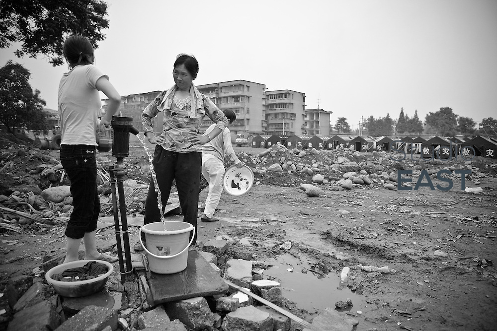 A young woman pumps water for another woman at one of the tent villages the government has set up for residents, in Dujiangyan, Sichuan province, China, on May 24, 2008. The death toll from China's earthquake on May 12 rose to 69,016 as of Sunday, June 1, a report from the China's Information Office of the State Council said. In addition, 368,545 were injured and 18,830 others were still missing in the 8.0-magnitude quake that jolted southwestern Sichuan Province and some neighboring areas. Photo by Chad Ingraham/Pictobank