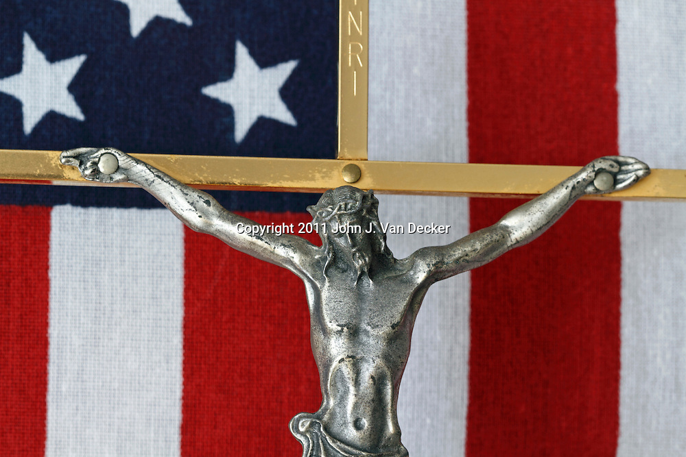 A Crucifix with an American flag in the background. This Crucifix lay on the casket of an American War Veteran.
