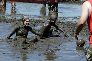 The more you play, the more mud you collect during MuddyGras, the 20th annual mud volleyball for Epilepsy at Wegerzyn Gardens MetroPark in Dayton, Saturday, July 10, 2010.